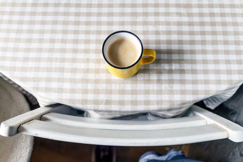 Um copo amarelo do café-chá está estando em uma tabela brilhante na luz do dia ensolarada Vista de acima fotos de stock
