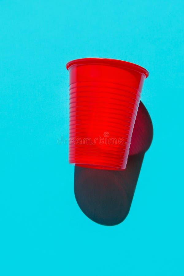 Um copo bebendo plástico vermelho no fundo azul contínuo Da natureza plástico-livre das alternativas da proteção ambiental vida a fotografia de stock