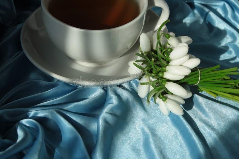 Um copo branco com chá verde em uns pires e um ramalhete pequeno dos snowdrops brancos da mola, amarrado com uma fita Ainda vida  fotografia de stock
