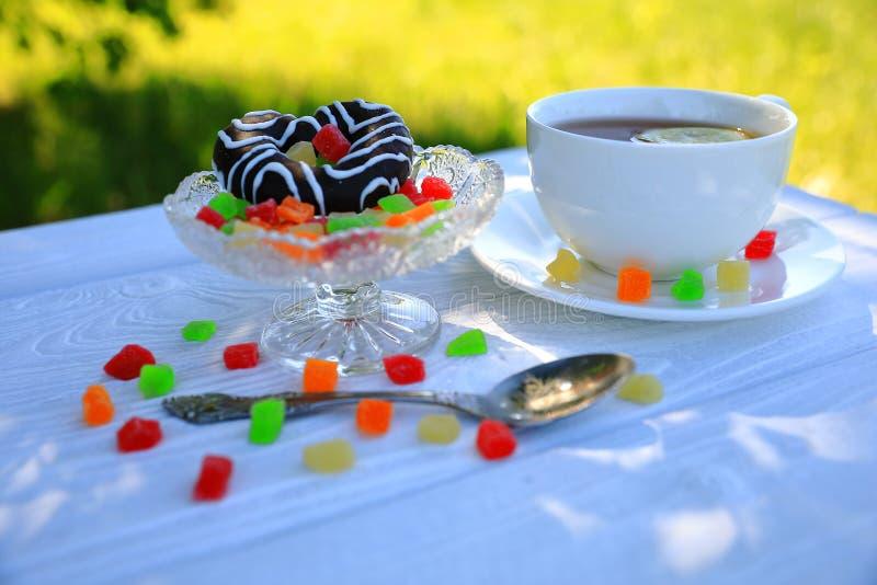 Um copo branco do chá, da cookie do chocolate e do doce de fruta foto de stock