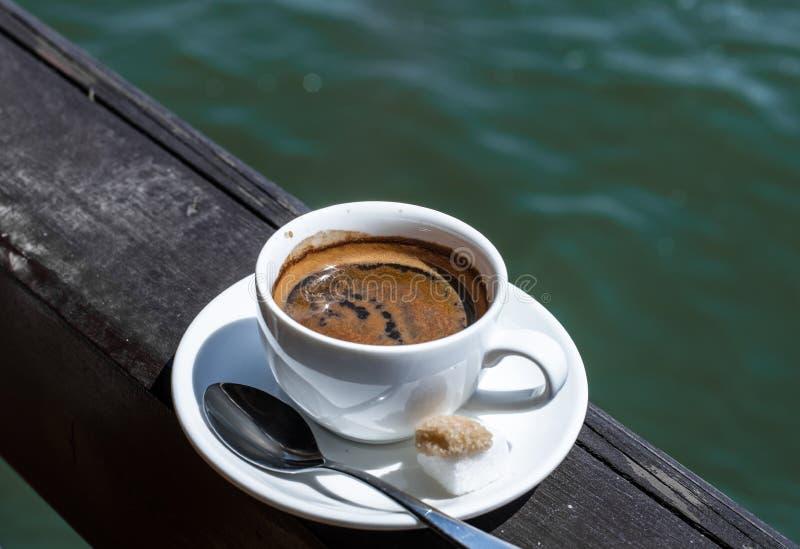 Um copo branco pequeno do café da porcelana em uns pires com uma colher de chá e duas partes de açúcar imagens de stock