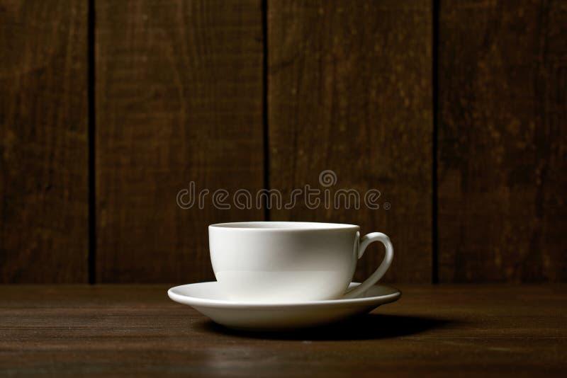 Um copo clássico do café ou de chá em um fundo de madeira escuro imagens de stock royalty free