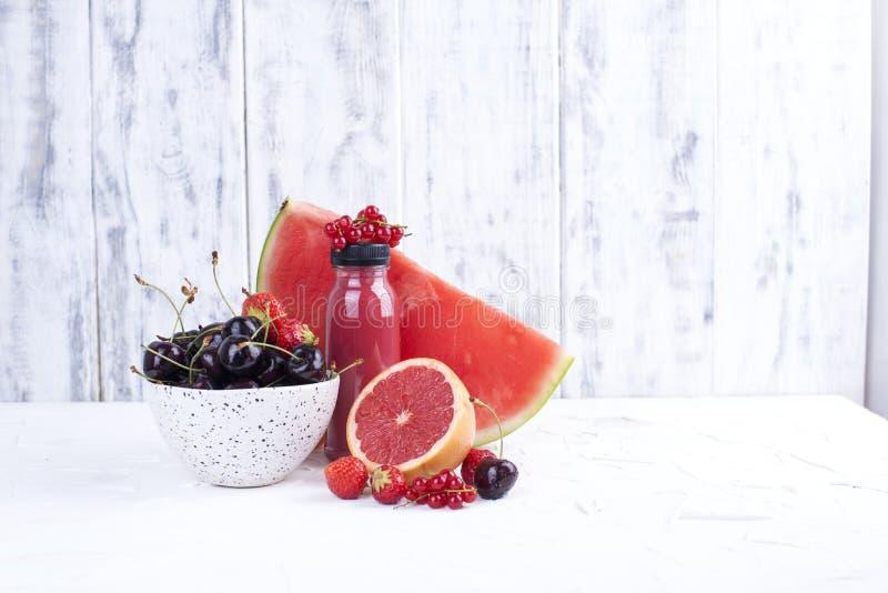 Um copo com cerejas maduras, toranja, framboesas, a melancia madura, uma garrafa do suco e um fundo branco Bagas do verão cópia imagem de stock