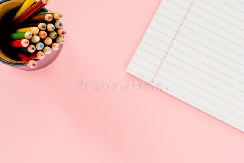 Um copo com lápis coloridos e um bloco de notas branco em um rosa liso SU fotografia de stock