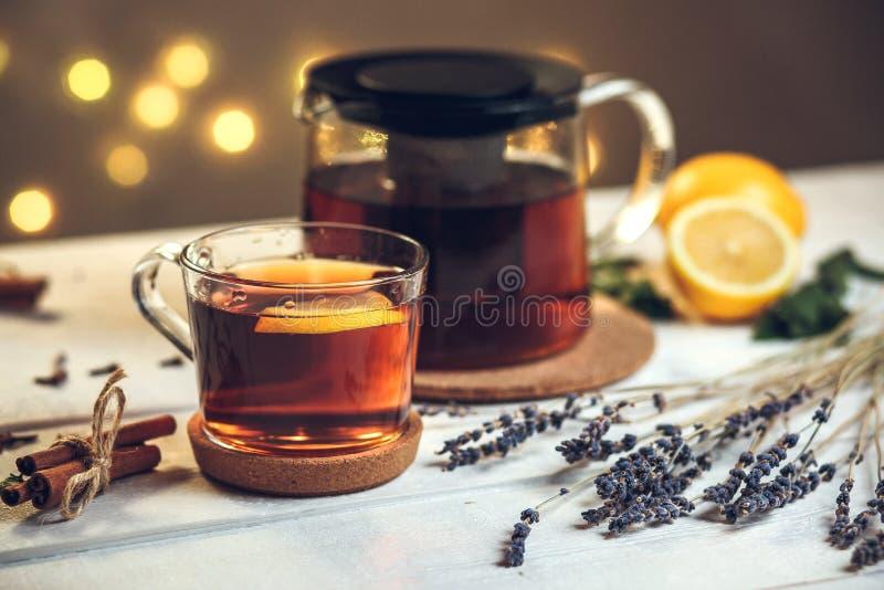 Um copo completo do chá preto com limão e bule imagens de stock
