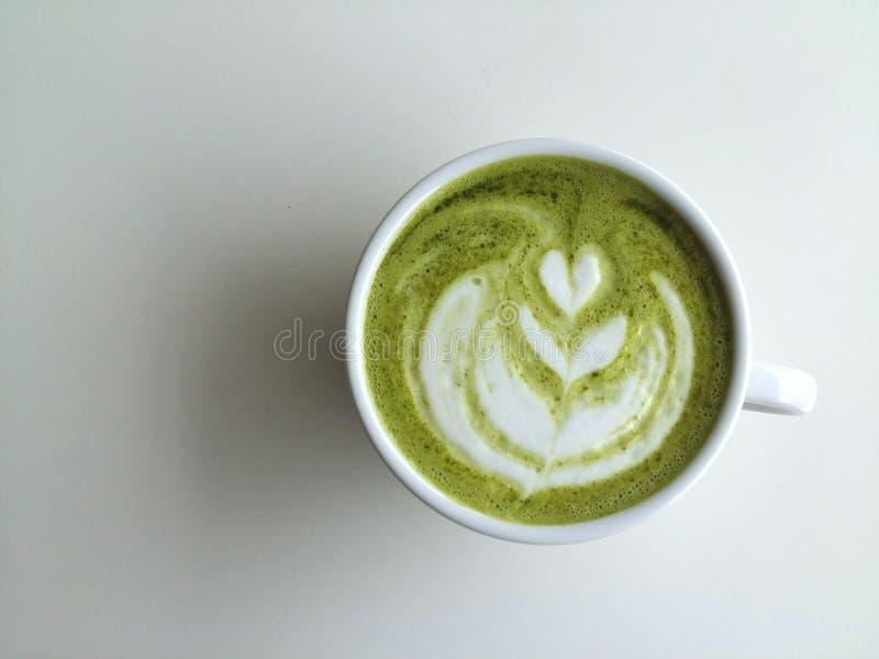 Um copo da arte do latte do matcha no fundo branco imagens de stock royalty free