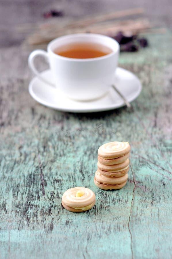 Um copo da tisana e de cookies quentes no fundo de madeira velho Copo da textura quente b do vintage das cookies do cozimento da  imagem de stock