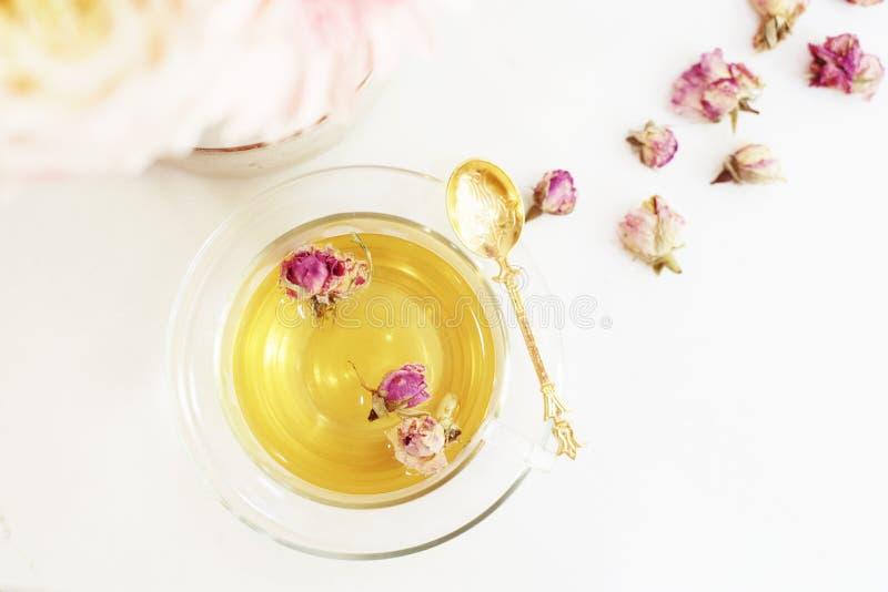 Um copo da tisana saudável com rosas secadas Flores frescas bonitas na tabela de mármore clara, vista superior Ramalhete cor-de-r imagens de stock