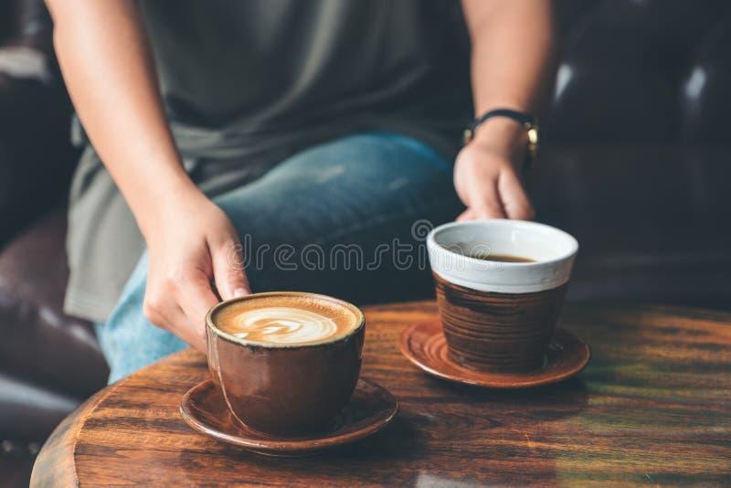 Um copo de café da terra arrendada e do serviço dois da mulher no café fotos de stock
