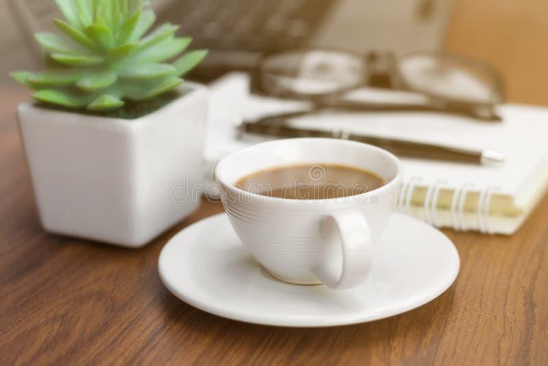 Um copo de café na mesa de escritório imagem de stock