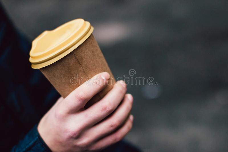 Um copo de café quente de papel na mão masculina imagem de stock royalty free