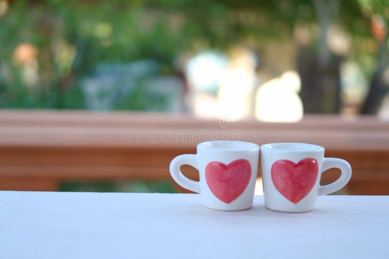 Um copo de chá do amor, um copo dos pares com sinal do coração para o dia do ` s do Valentim imagem de stock