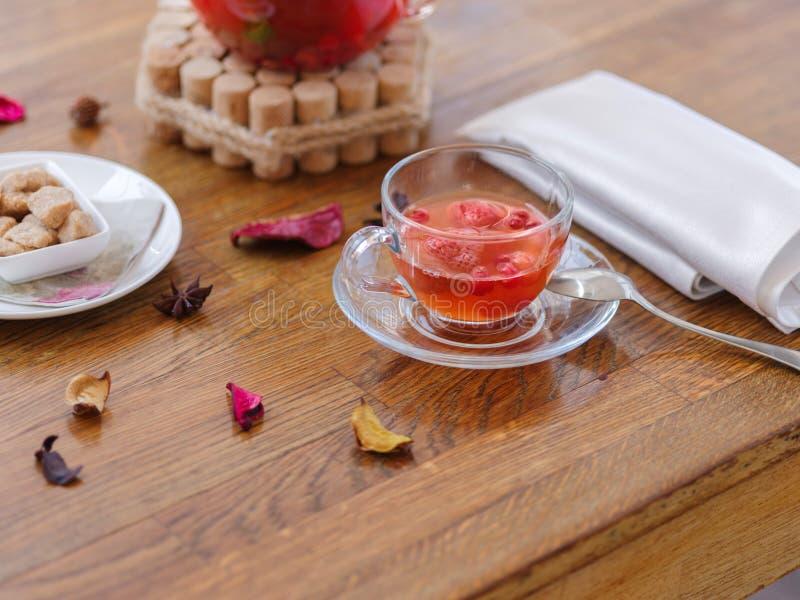 Um copo de vidro do chá com partes de morangos e corinto vermelho, colher metálica, e um guardanapo de tabela em uma tabela de ma imagem de stock royalty free
