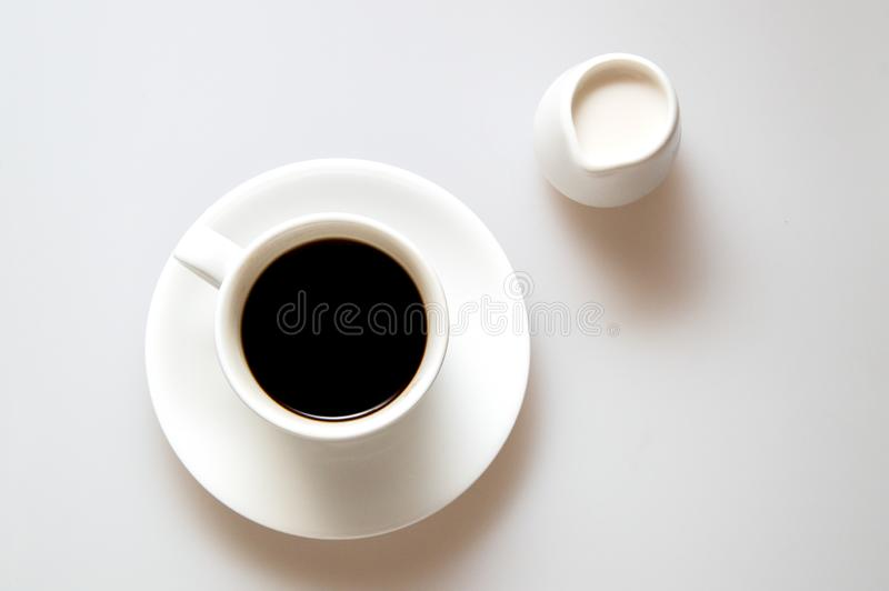 Um copo do café e do creme fortes no fundo branco foto de stock
