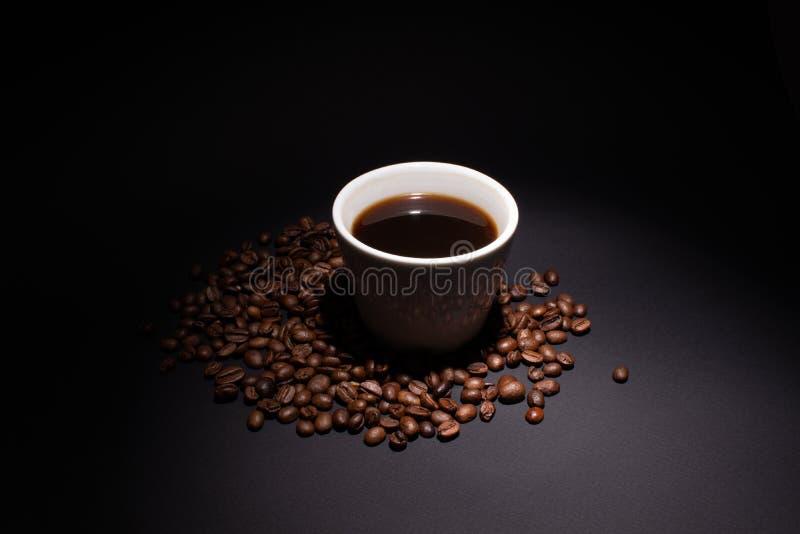 Um copo do café forte em uma superfície escura é iluminado no direito com um destaque imagem de stock royalty free