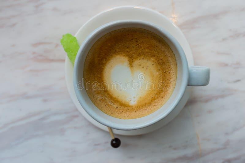 Um copo do café do latte com teste padrão do coração em um copo branco no fundo de mármore branco e o açúcar verde colam imagens de stock