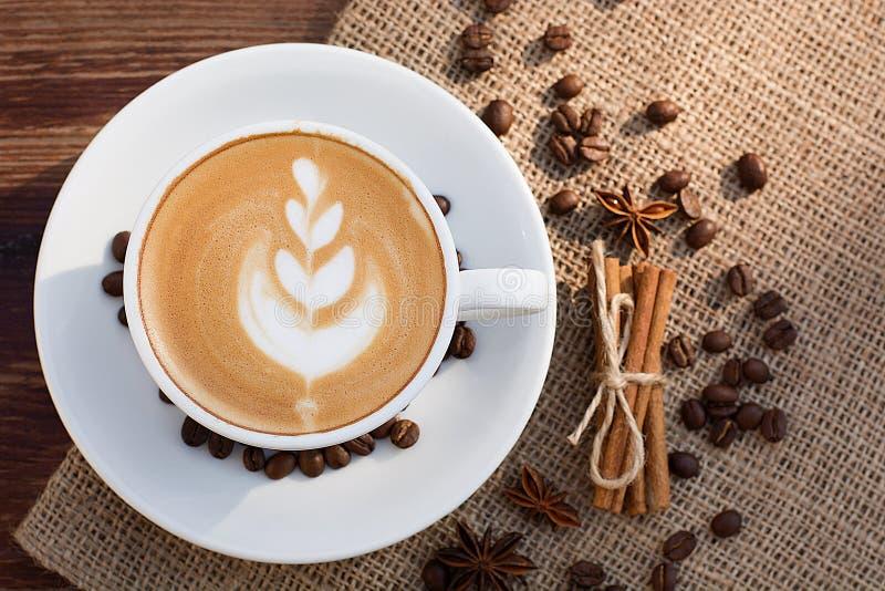 Um copo do café do latte e dos feijões de café foto de stock royalty free