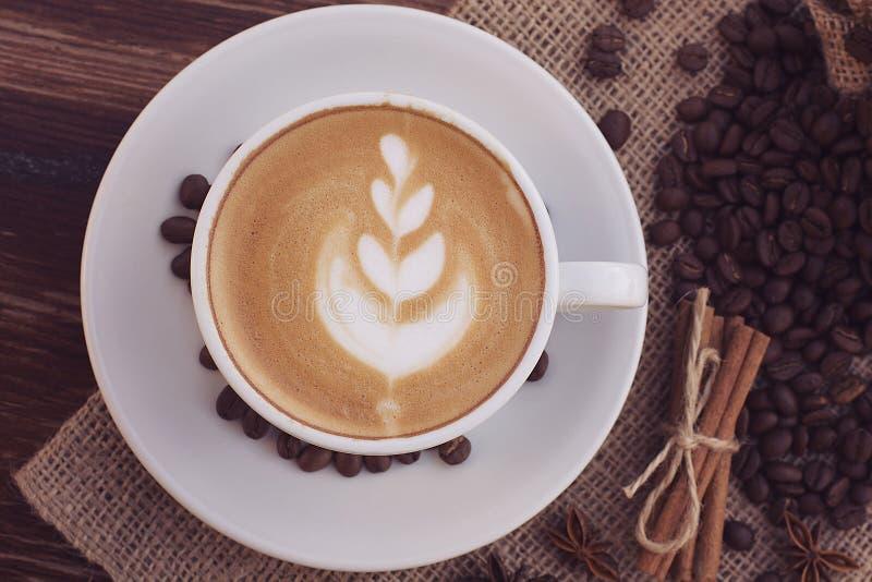 Um copo do café do latte e dos feijões de café foto de stock