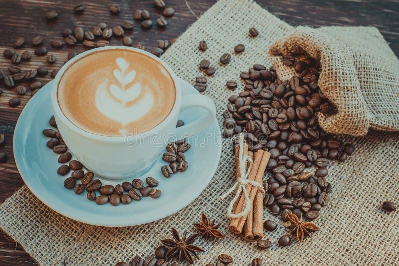 Um copo do café do latte e dos feijões de café toning foto de stock royalty free