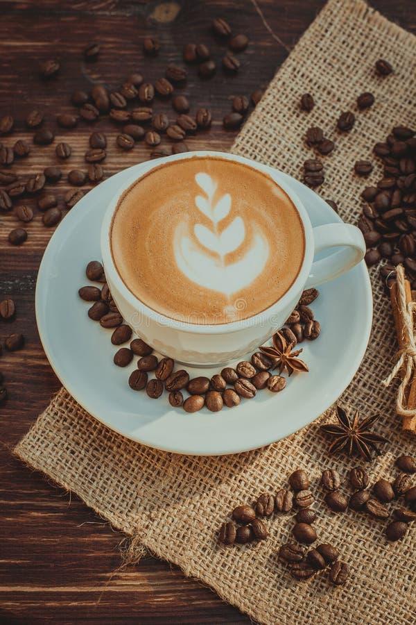Um copo do café do latte e dos feijões de café toning imagem de stock