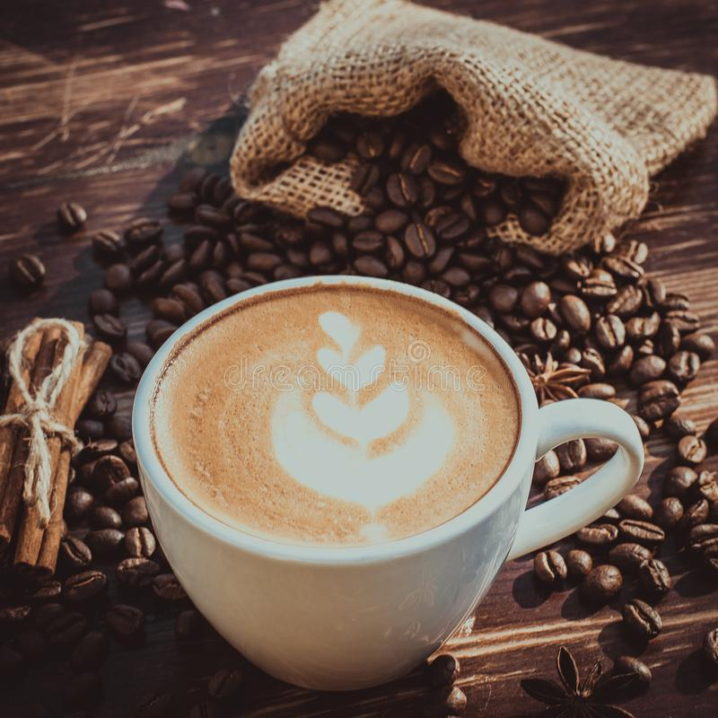 Um copo do café do latte e dos feijões de café toning fotografia de stock royalty free