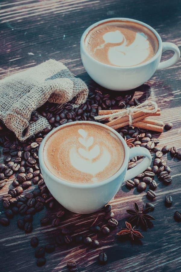 Um copo do café do latte e dos feijões de café toning fotos de stock