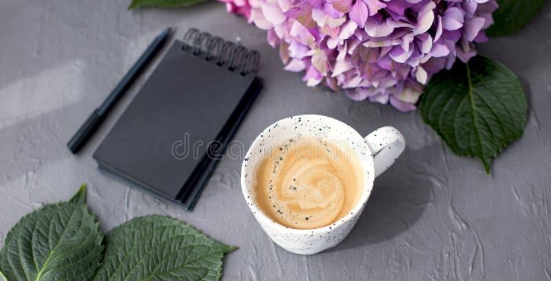 Um copo do café perfumado da manhã e da hortênsia cor-de-rosa floresce, em um fundo cinzento, em um espaço livre para o texto e e fotos de stock royalty free