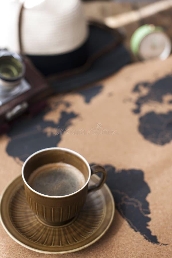 Um copo do café perfumado no mapa, em uma câmera velha e em uma rota p imagens de stock