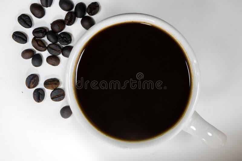 Um copo do café preto e do nenhum açúcar com os feijões de café roasted sobre foto de stock royalty free