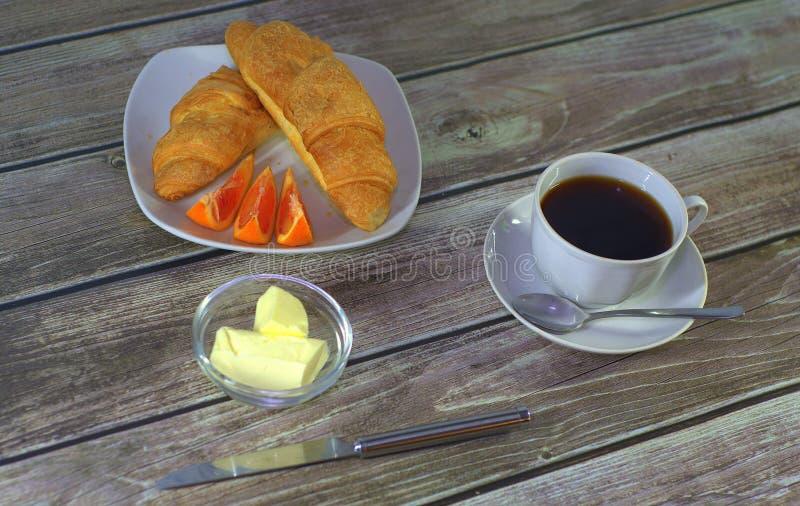 Um copo do café preto em uns pires com uma colher, uma placa com croissant e fatias do limão com suporte da manteiga em uma tabel fotografia de stock