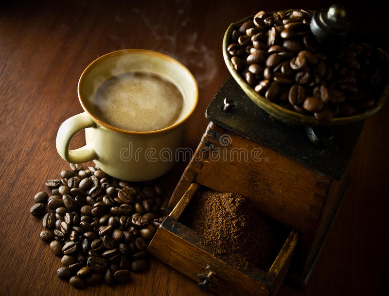 Um copo do café quente, e um moedor de café antigo foto de stock