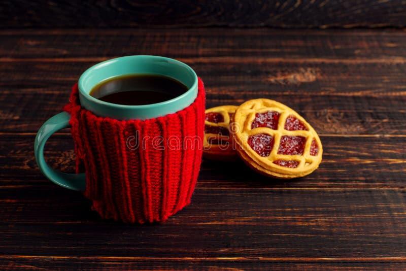 Um copo do café quente, em uma tampa feita malha e em umas cookies caseiros, mentira em uma tabela de madeira imagem de stock royalty free