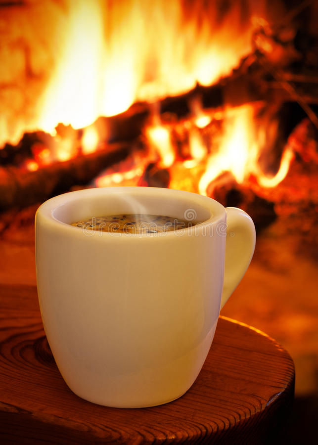 Um copo do café quente na frente da chaminé fotografia de stock