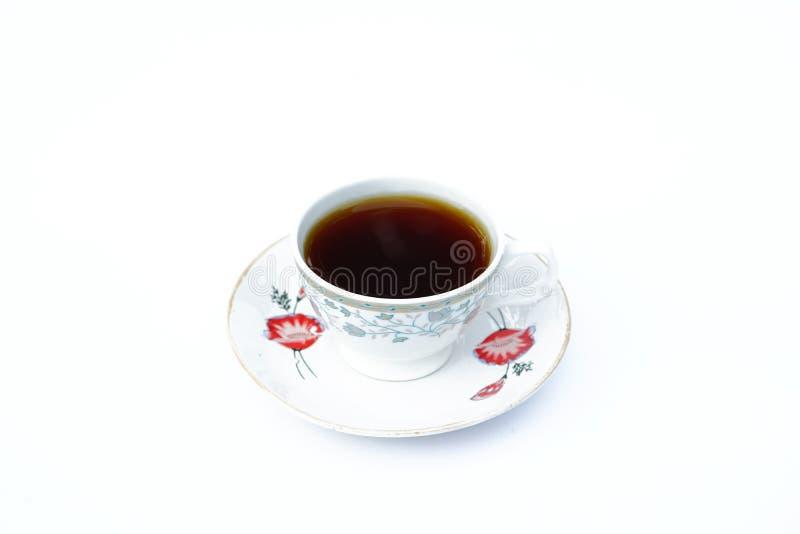 Um copo do café vermelho em uma placa com fundo branco cor imagem de stock