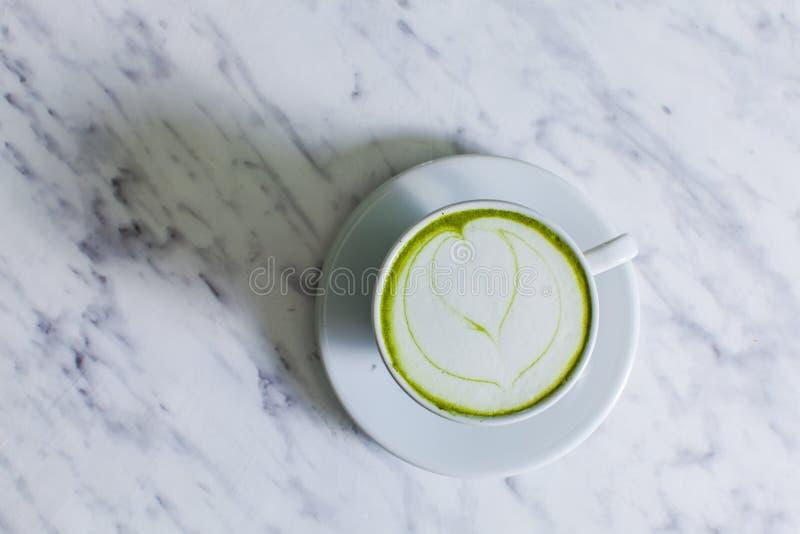 Um copo do cappuccino de Matcha com arte do latte em uma tabela clara foto de stock