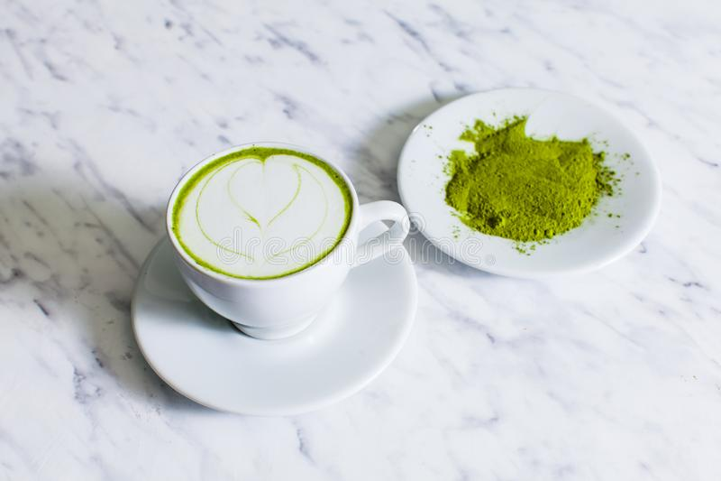 Um copo do cappuccino de Matcha com chá pulverizado de Matcha fotos de stock royalty free