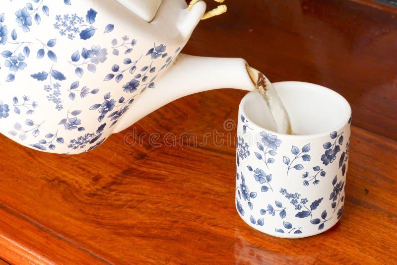 Um copo do chá com o bule no fundo imagens de stock