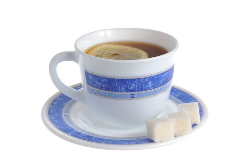 Um copo do chá com uma fatia de limão dentro e de açúcar refinado sobre foto de stock royalty free