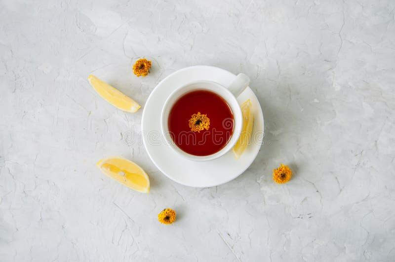 Um copo do chá da flor com limão em um fundo de pedra branco Stil fotografia de stock