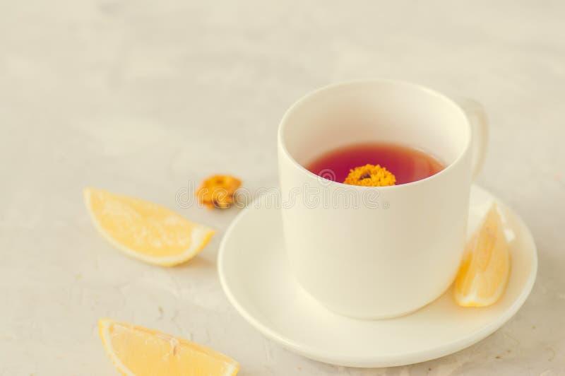 Um copo do chá da flor com limão em um fundo de pedra branco Stil fotos de stock