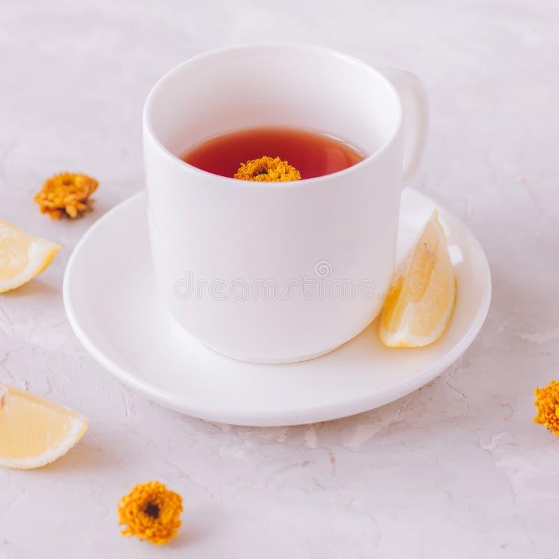 Um copo do chá da flor com limão em um fundo de pedra branco Stil foto de stock