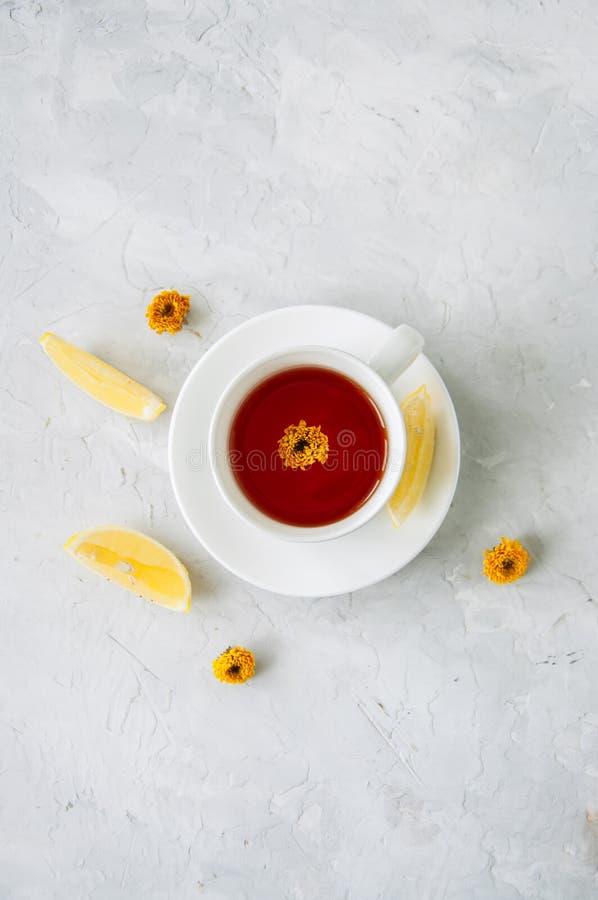 Um copo do chá da flor, das fatias do limão e de flores secadas em um branco imagens de stock royalty free
