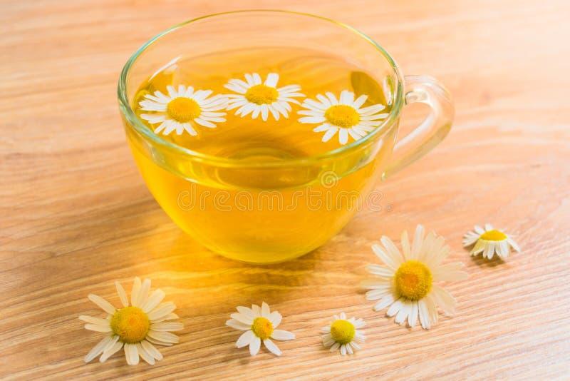 Um copo do chá de camomila em uma tabela de madeira Tisana terapêutica fotos de stock