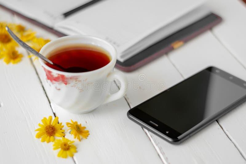 Um copo do chá e um bloco de notas com pena fotos de stock royalty free