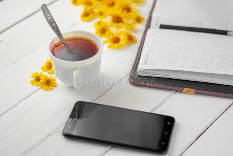 Um copo do chá e um bloco de notas com pena imagens de stock royalty free