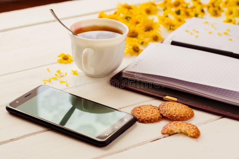 Um copo do chá e um bloco de notas com pena fotos de stock