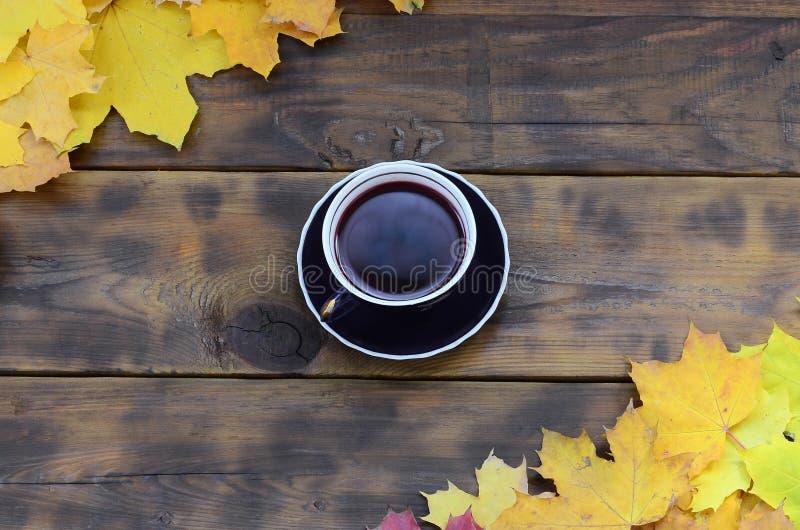 Um copo do chá entre um grupo de amarelar as folhas de outono caídas em uma superfície do fundo de placas de madeira naturais do  foto de stock