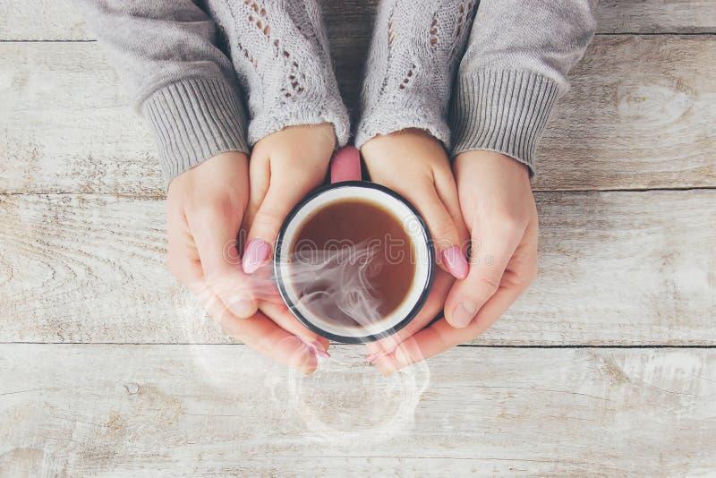 Um copo do chá nas mãos de um homem e de uma mulher imagem de stock