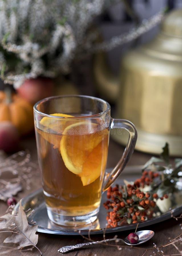 Um copo do chá perfumado com fatias alaranjadas em uma bandeja de prata, uma colher azul foto de stock