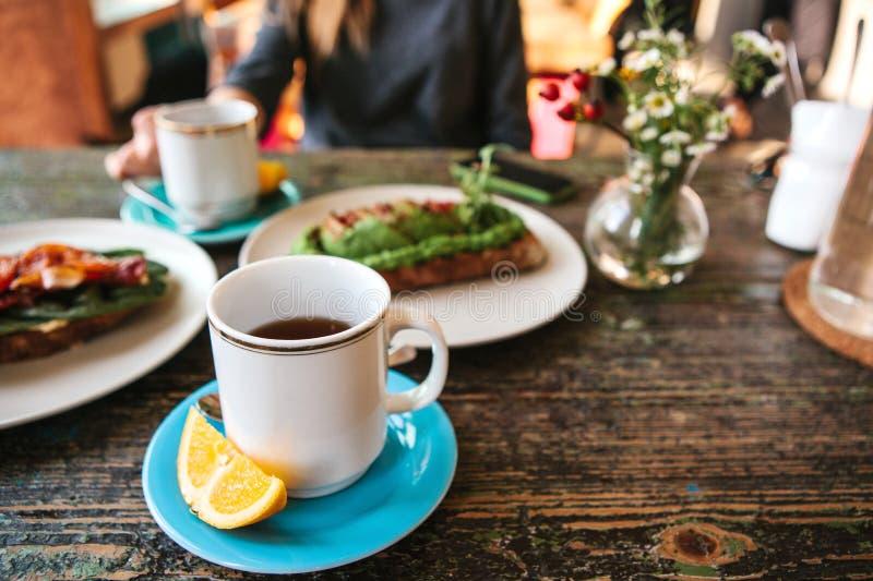Um copo do chá perfumado fresco e ao lado do brinde ele e dos sanduíches nutritivos e deliciosos encontra-se na tabela A menina fotografia de stock royalty free
